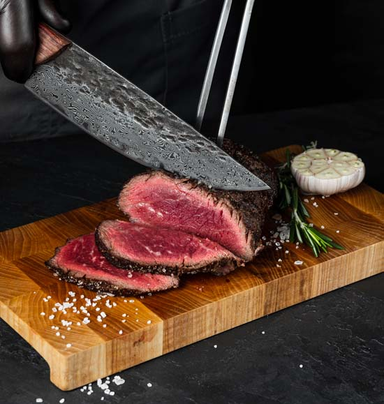 damascus chef knife slicing delicious meat